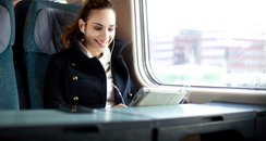 Young woman on train with iPad