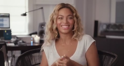 Beyonce smiling in a white shirt