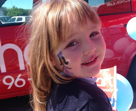 Little girl with facepaint and flag.
